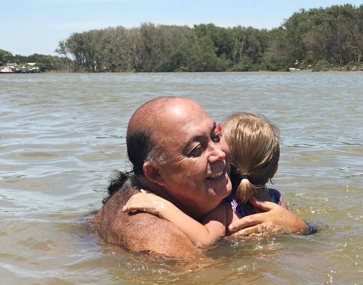 Victor Aquino iniciando a neta Maju nos mistérios do encontro das águas do Pontal de Atafona